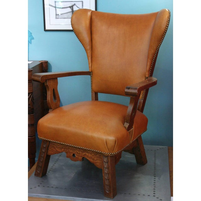 Unusual wing chair with carved detail on front, and drama on the back. Lovely original condition. Avantgarden Ltd....