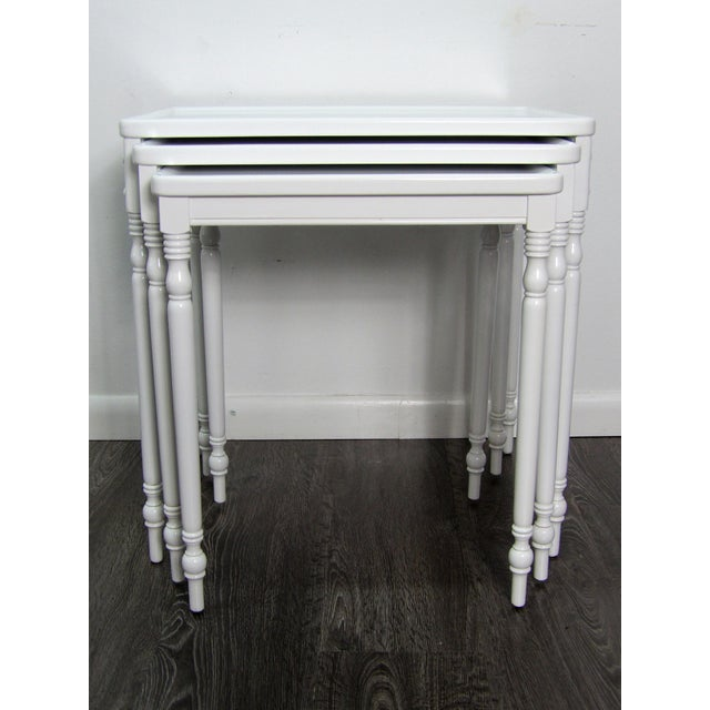Crisp white lacquered wood nesting tables, set of three. This vintage set has new finish giving them a modern /...