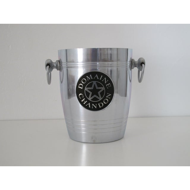Aluminum ice bucket by French champagne company Domaine Chandon. Bucket has loop handles on each side for transport.