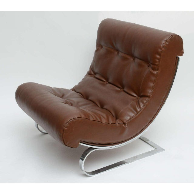Pair of Formanova club lounge chairs on flat chromed steel base. A C-curved self-stabilizing base with brown leather....