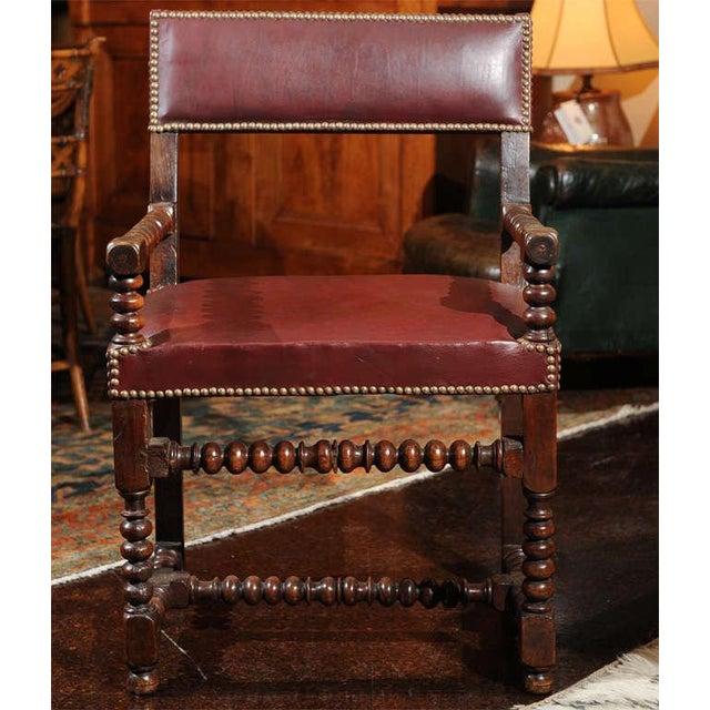 Bobbin Turned Walnut Armchair with Red Leather Upholstery and nailhead trim; French circa 1800.