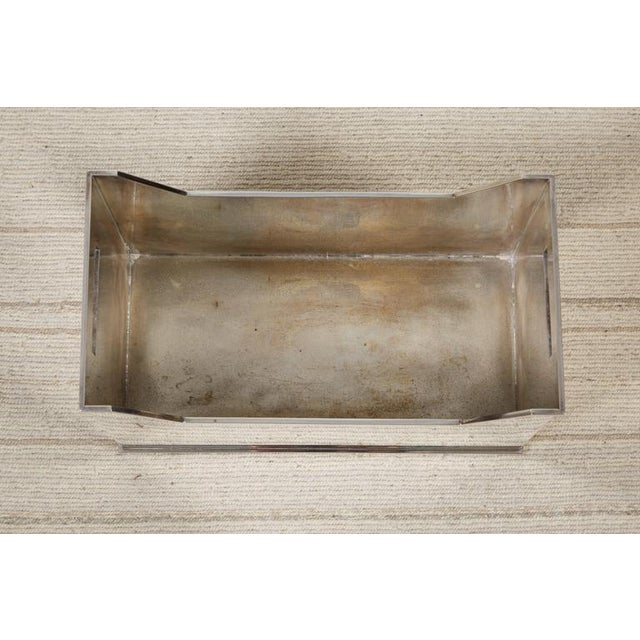 A rectangular silvered metal container with handles. Unmarked. Made in the late 20th century.