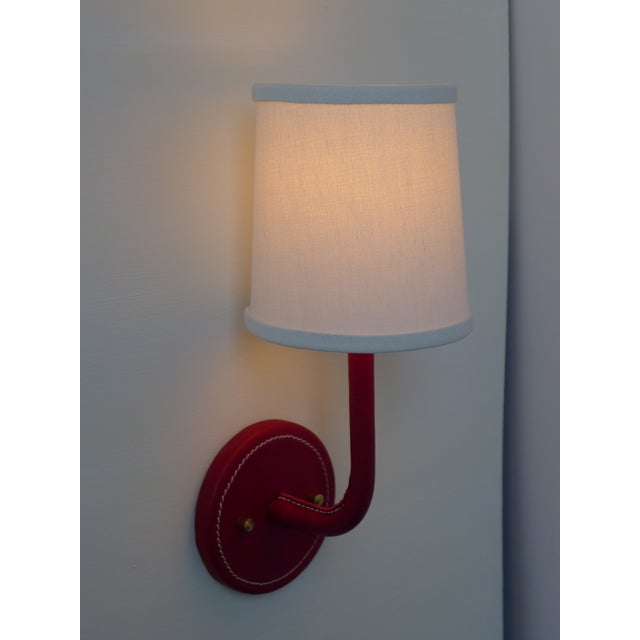 Paul Marra Leather Wrapped Adnet inspired wall sconce, shown in red, with top-stitched detailing. Top-stitching detail is...