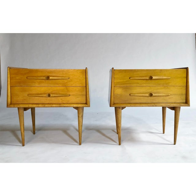 Pair of mid-century Edmond Spence two-drawer nightstands or bedside cabinets in light wood, raised edges and tapered legs....