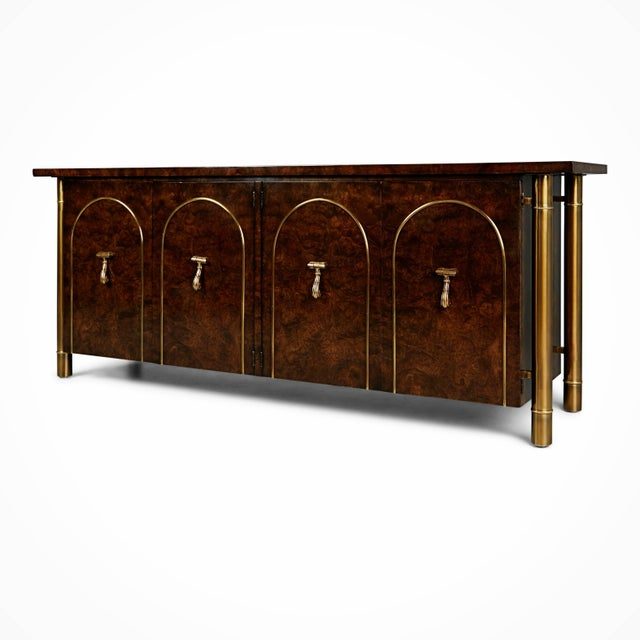 This Asian inspired credenza by William Doezema for Mastercraft features a burl wood finish with brass cylindrical legs...