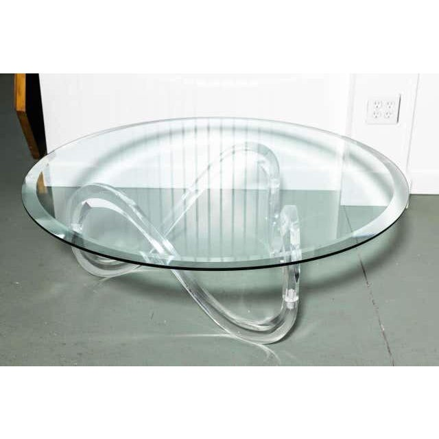 Bevelled glass coffee table with serpentine Lucite base, the base comes in three sections with locks together. This table...