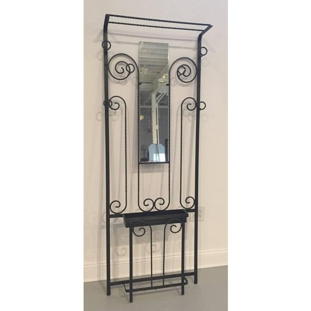 This French Art Deco hand-wrought iron hall tree dates from the 1930s. The stand has a central mirror, six hangers for...