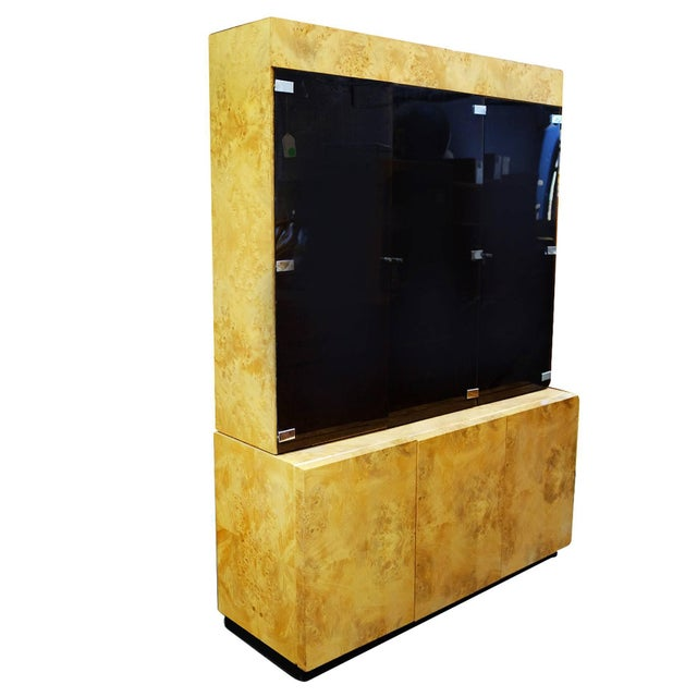 Large Postmodern burl elmwood cabinet featuring a breakfront with three smoked glass doors containing adjustable shelves...