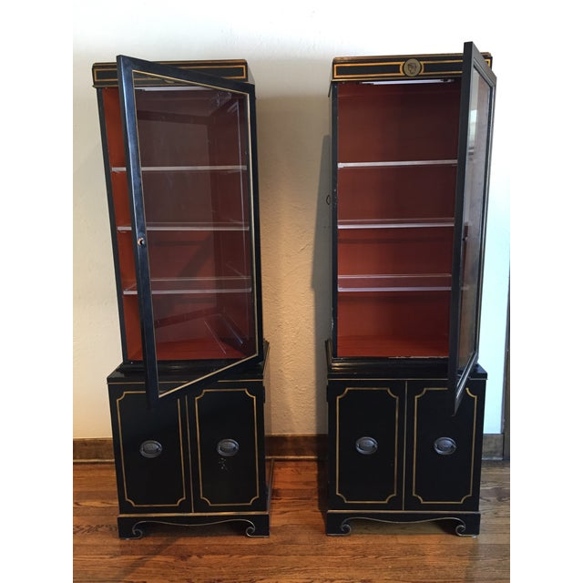 A very unique pair of black vitrines in a petite size. Highlights of this piece are the gilt detailing, unique decorative...