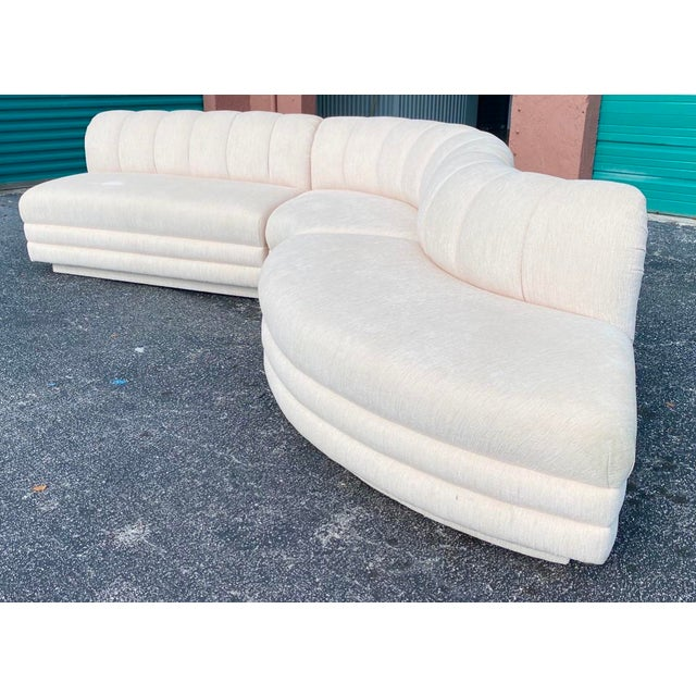 Amazing contemporary three piece sectional sofa. Done in a champagne boucle with a serpentine curve. The bottom half of...
