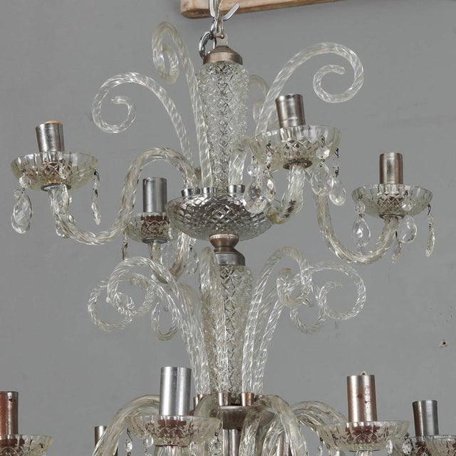 Clear Murano glass chandelier with twelve lights total on two tiers, circa 1930s. Bottom tier has eight candle arms with...