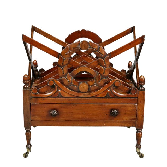 With divider top and carved wreaths at each end over a drawer raised on turned legs and casters.