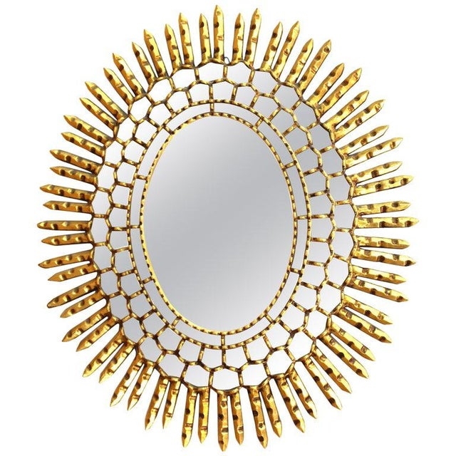 Mid-Century Modern oval shaped sunburst wall mirror. The piece is made of giltwood with inserted concentric circles of...