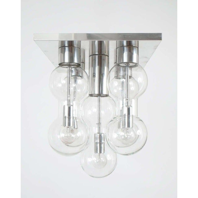 Beautiful flush mount with five hourglass shaped glass vessels each containing a single bulb. It's in excellent condition....