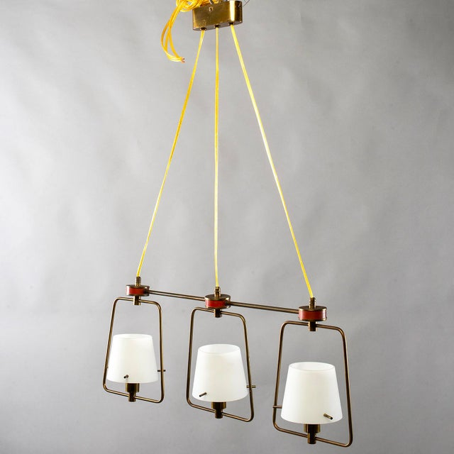 Stilnovo style Italian three light fixture, circa 1960. Brass tubing frame was red enamel accents and features adjustable...
