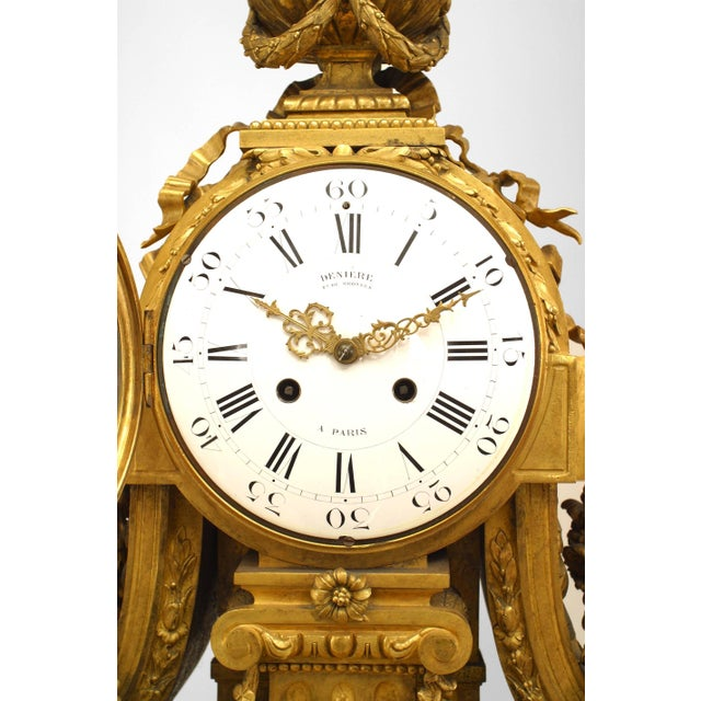 French Louis XVI style (19th Century) gilt bronze mantel clock with a centre fluted column supporting the clock face...