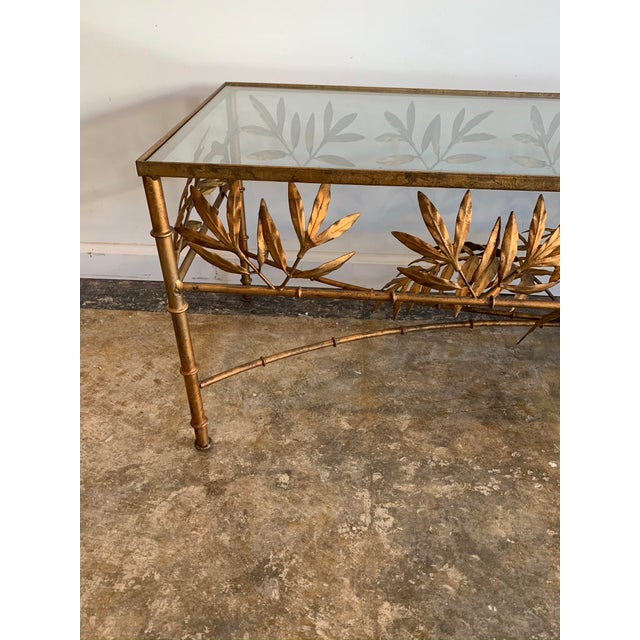 Vintage mid-century Italianate gilded metal coffee table with bamboo stalk and leaf design and glass top. Classic and...