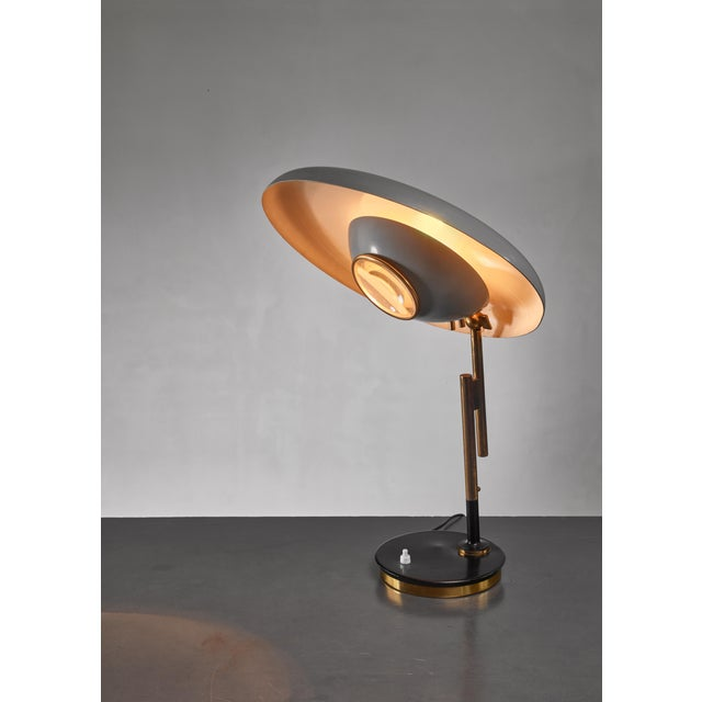 A model 555 table lamp by Oscar Torlasco for Lumi Milano in perfect condition. The brass and metal swiveling lamp has a...