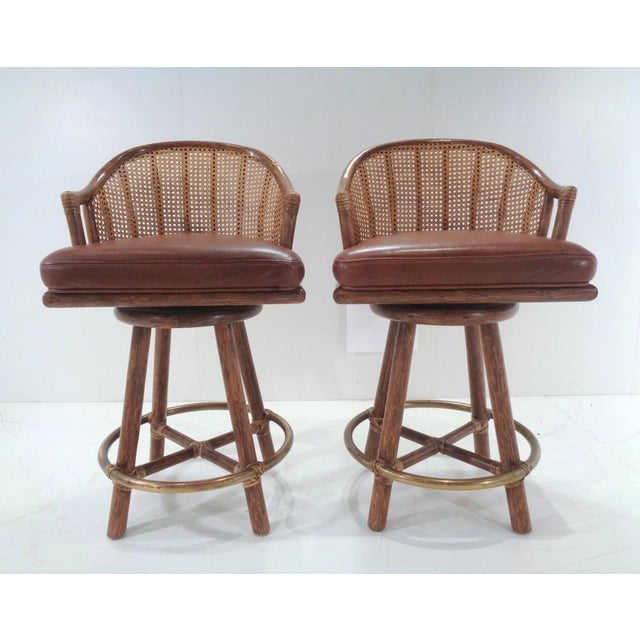 Handsome pair of 1970' s McGuire of San Francisco swivel bar stools in good condition. Classic McGuire design excellence...