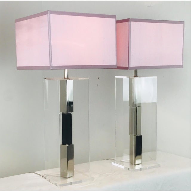 Pair of Lucite and chrome table lamps by Laurel. Chrome bars stacked in the center of a Lucite box. New Pink Silk shades...
