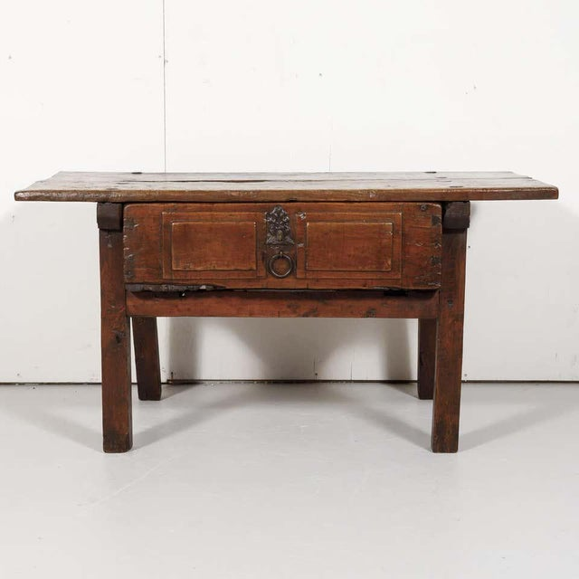A rustic early 18th century side table handcrafted of solid walnut near Valencia, Spain, circa 1720s. Soundly constructed...