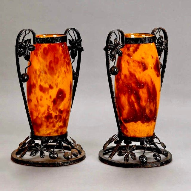 Pair of tall French art glass vases in warm tortoise and amber tone with black iron surrounds with large, curved handles...