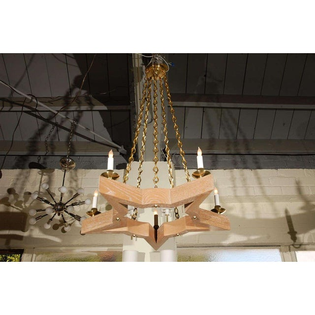 Paul Marra Star Chandelier shown in oak and brass. Ceruse Oak, brass hardware, paper candle sleeves. Five Candelabra base,...
