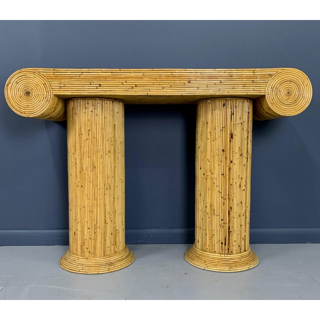 This classically styled console table with a column and scroll design is executed in a lacquered small diameter bamboo....