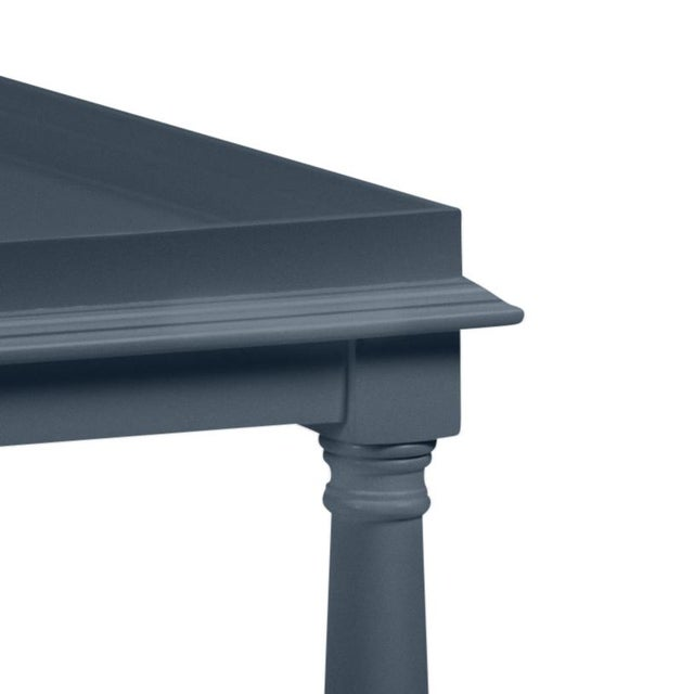 Made of acacia wood, this cocktail table feartures a gallery shelf and turned legs. The color is Benjamin Moore Hale Navy...