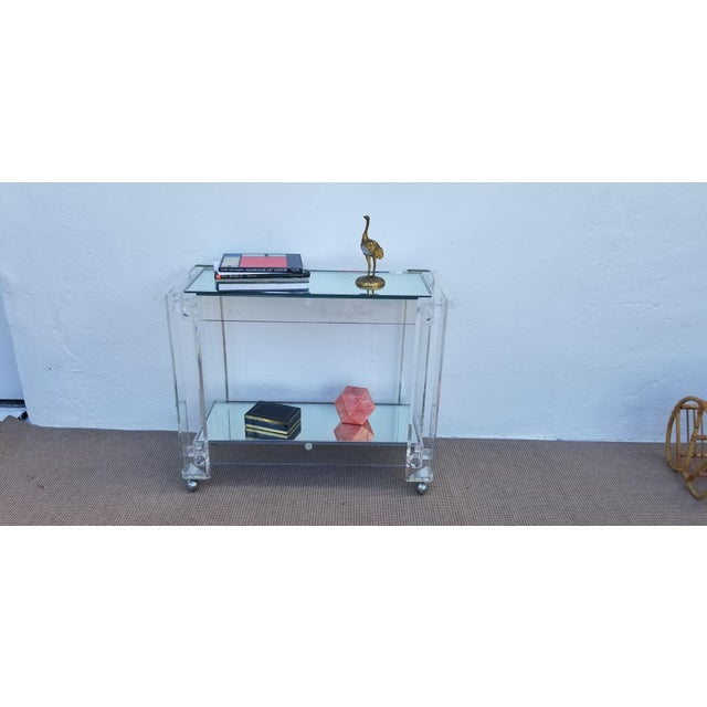 This vintage Lucite bar or trolley cart has two tiers with mirrored glass tops. The original chrome wheels have been...