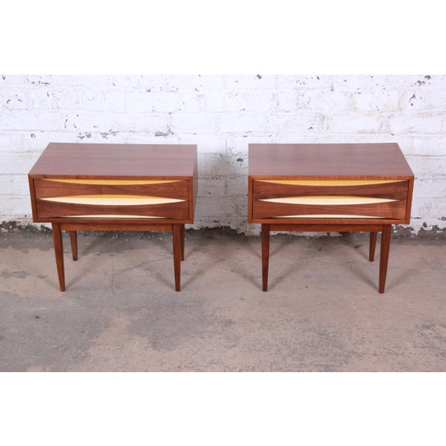 An exceptional pair of mid-century modern walnut nightstands by West Michigan Furniture. The nightstands have a beautiful...