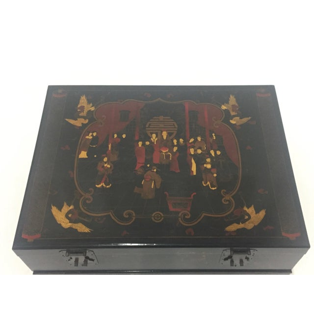 An intriguing chinoiserie coffee table in black, gold, and red having a beautifully decorated box with original hardware...