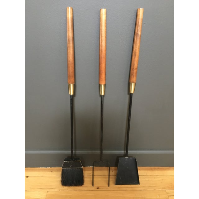 Mid-century wood-handled wrought iron fireplace tool set by Seymour Manufacturing. Set includes three fireplace tools and...