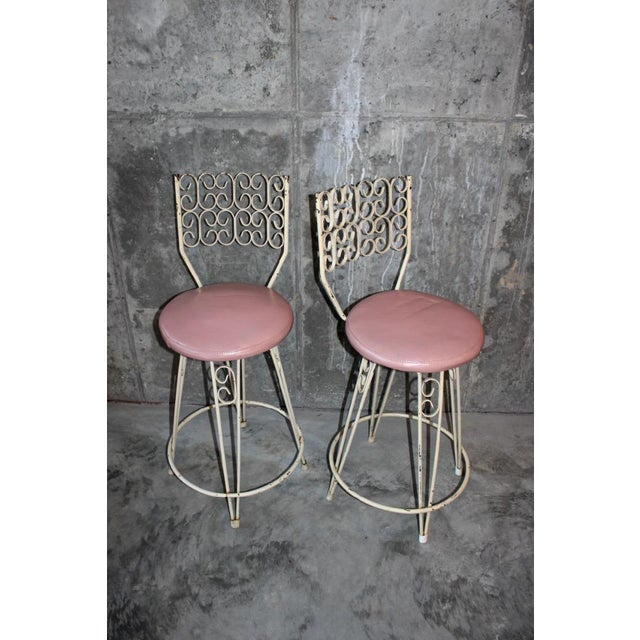 Unique pair of wrought iron vintage swiveling bar stools with hairpin legs and detailed backs. Designed by Arthur Umanoff...