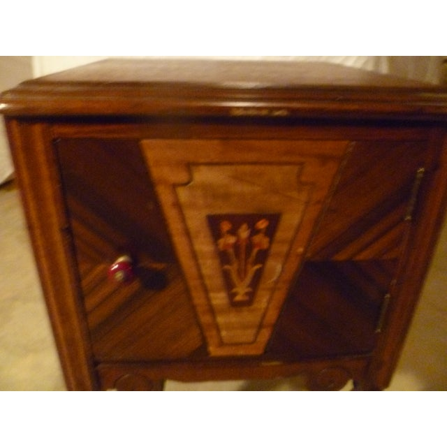 This is a 19th century bed stand. Rich in color tones. Inlaid color flowers in wood . Original door pull in burgundy. One...
