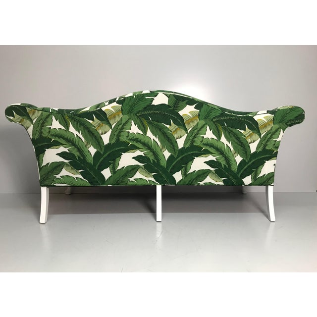 Newly upholstered, camel back sofa in a durable, indoor/outdoor, tropical leaf fabric. Painted, carved wood legs. Rolled...