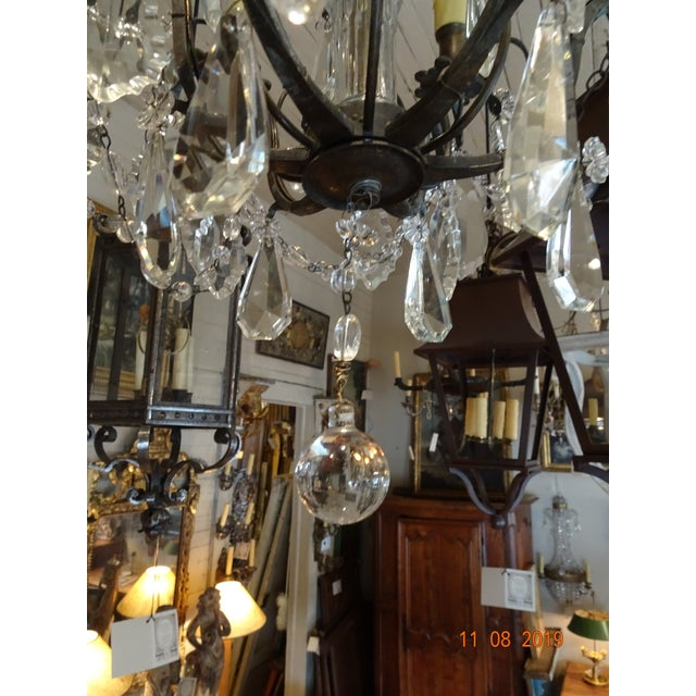 Exquisite small crystal chandelier with black iron frame. 3 tiers with swags of crystals and pendalogue crystals as well....