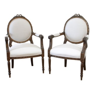 20th Century Pair of Aged Giltwood Ribbon Carved Open Arm Chairs For Sale
