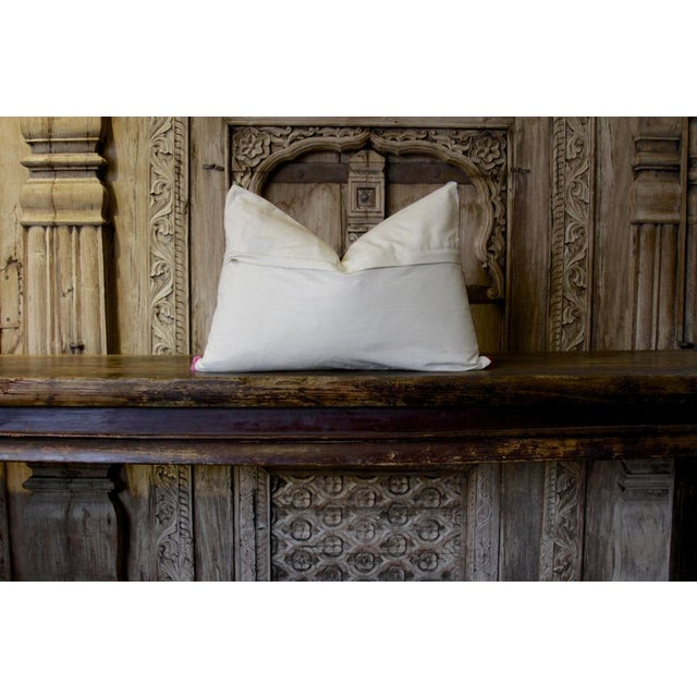 Crafted using vintage hand-embroidered textile, this pillow is accented with bold floral designs, mirror work, and pom...