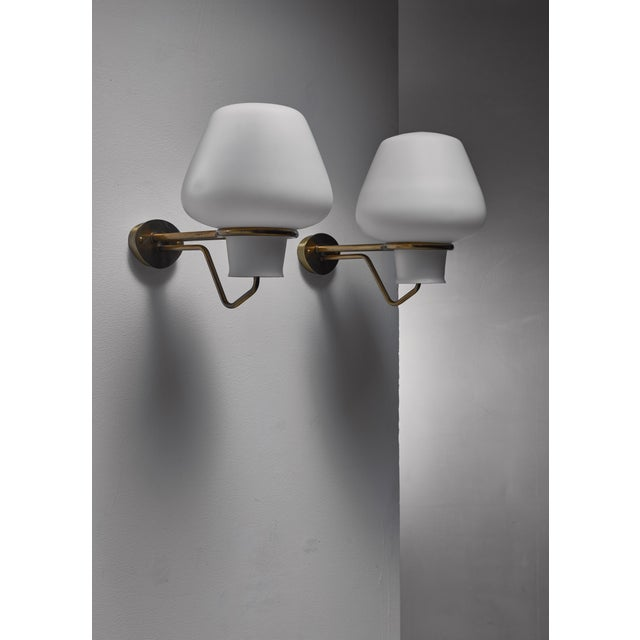 A pair of elegant Swedish wall lamps from the 1950s. From the oval brass wall mount two arms extend that hold both the...
