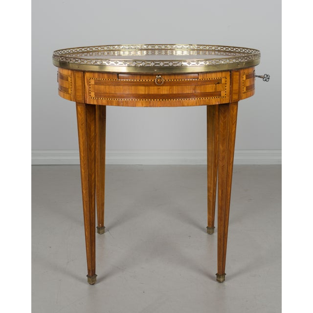 French Louis XVI style bouillotte table made of veneers of rosewood, tulipwood and mahogany. Two dovetailed drawers and...
