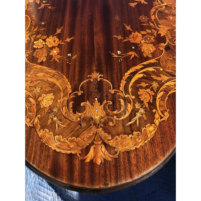 A beautifully shaped marquetry center or side table having serpentine moulded top with scrolling foliate, floral and...