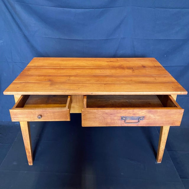 This early but refinished pine table from Lyon, France has a rich patina and two drawers and could be used as a desk, side...