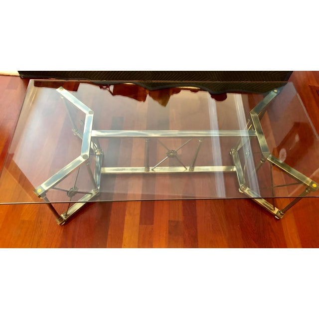 Large thick removable glass top that sits on a unique base with floral details. This neoclassical style coffee table is...