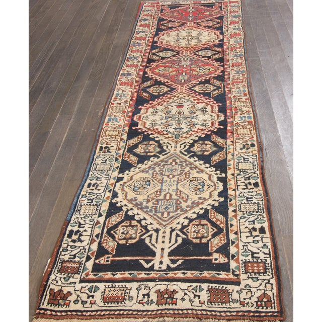 Vintage hand-knotted Persian rug with a geometric design on a navy blue field. This rug has a great color scheme and very...