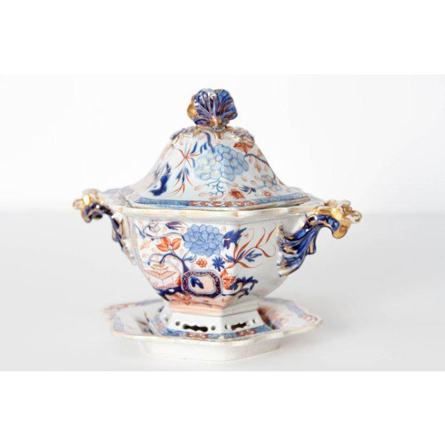 A English soup tureen with under plate decorated with a colorful Imari design. Overall floral scene with pagodas in...