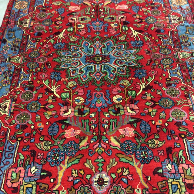 This is a vintage Nahavand Persian rug that was handmade in the 1980s. The piece features a medallion flower amidst a...
