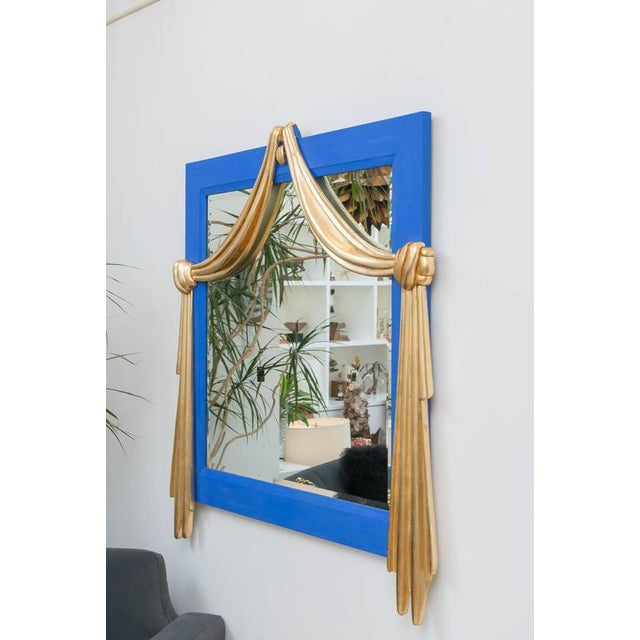 Large-scale mirror p that has been painted in a French flat blue paint with gilt draped detail.