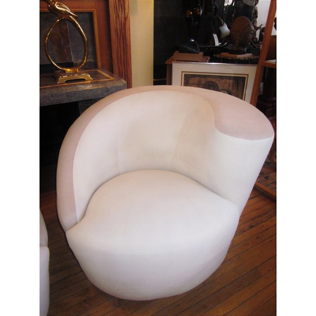 """This is a sleek, cool, and chic pair of 1980s era Vladimir Kagan """"Nautilus"""" swivel chairs in a creamy white. The accent..."""
