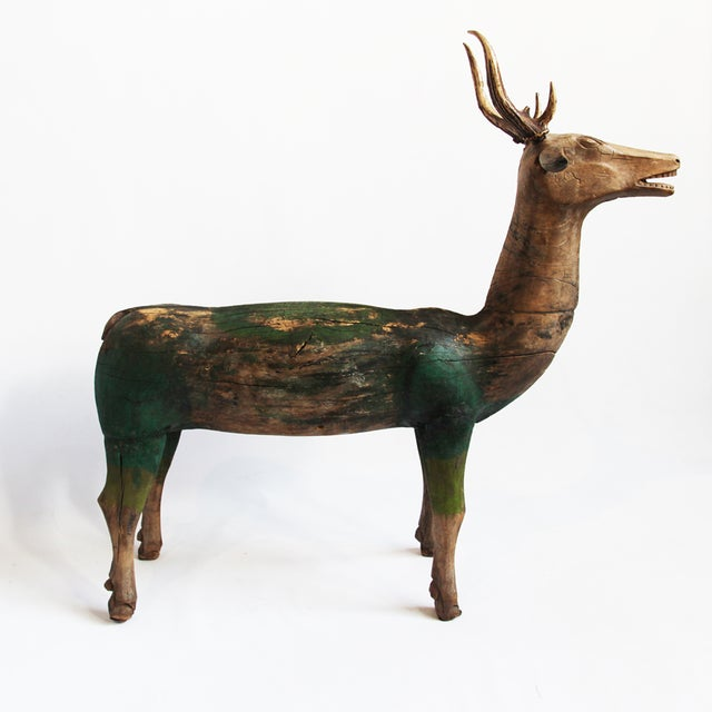 Vintage Javanese hand-carved wood deer with antlers. Features an aged green paint. Aged wood shows cracks and detail of...